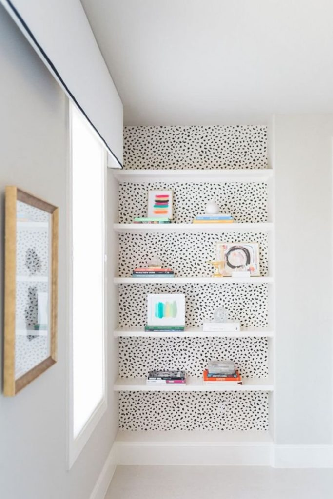 Dalmation spot print peel and stick wallpaper backing a built-in bookshelf.